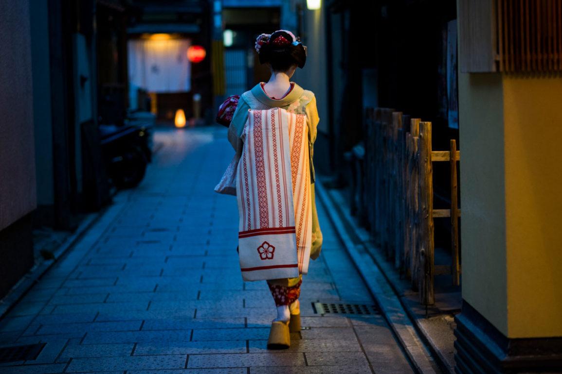 geisha o maiko de espaldas paseando por una calle a oscuras