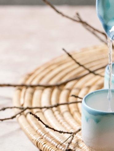 jarra sirviendo sake sobre un vaso de cerámica